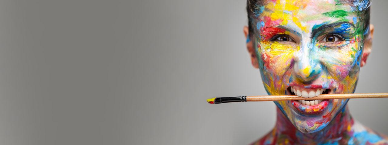 Frau mit bunter Farbe im Gesicht undPinsel im Mund
